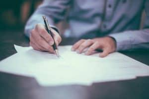 אדם חותם על מסמכים